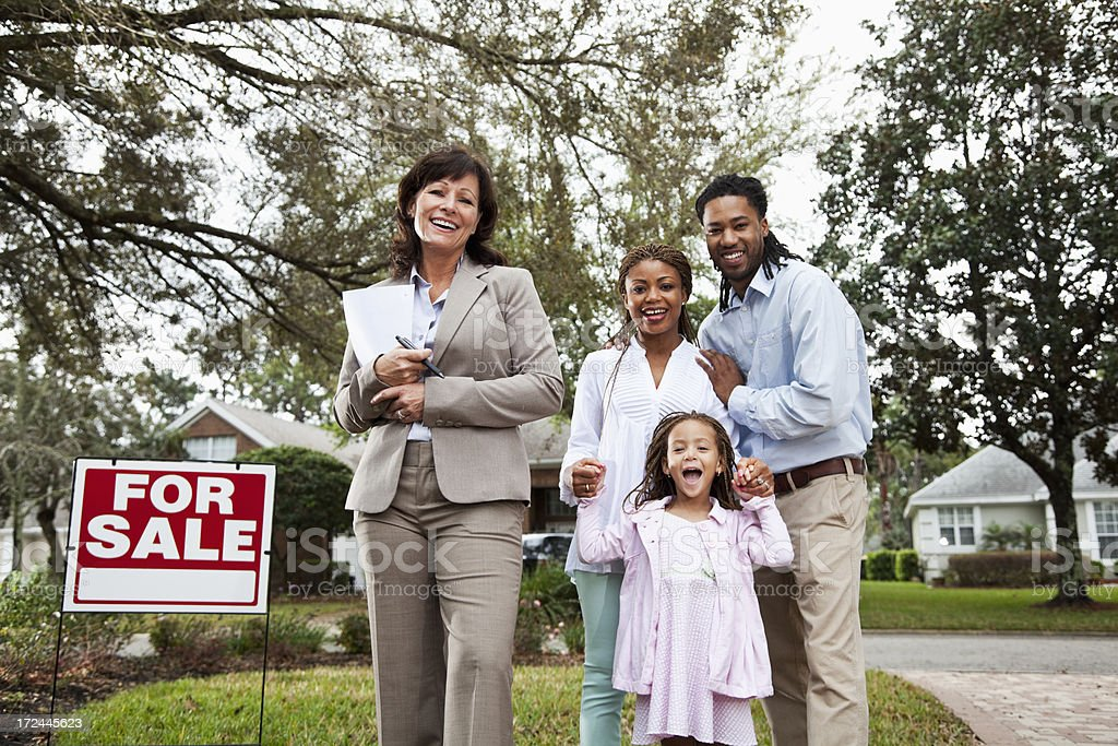 Real estate agent with family outside house royalty-free stock photo