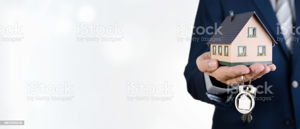 Real estate agent with home keys and house miniature stock photo