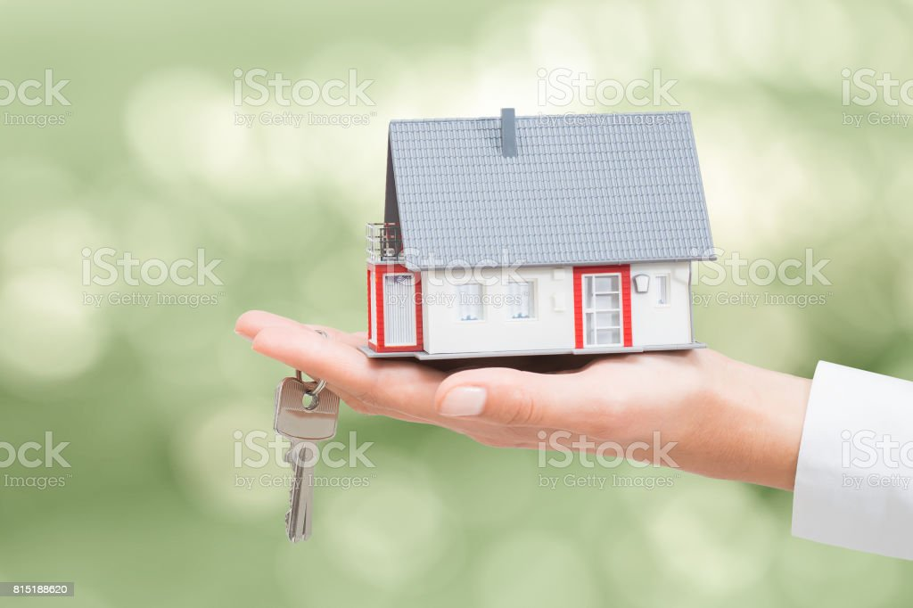 Real estate agent with house model and keys. stock photo