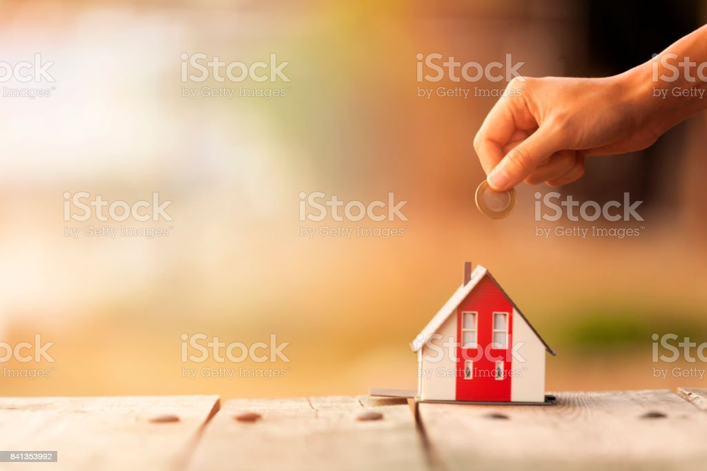 Real Estate Agent with house model and saving concepts stock photo