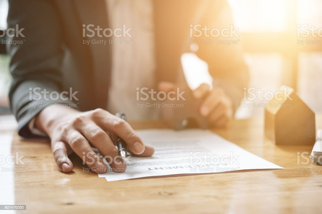 Real estate agent with house model hand putting signing contract,have a contract in place to protect it,signing of modest agreements form in office.Concept real estate,moving home or renting property stock photo