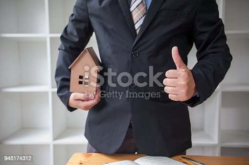 885968454istockphoto Real estate agent with house model 945174312