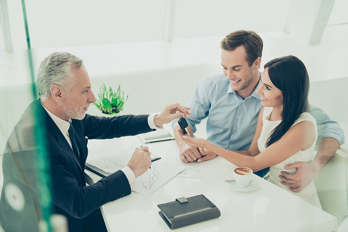 938640610 istock photo Real estate agent working with couple of customers and giving them keys 949554106