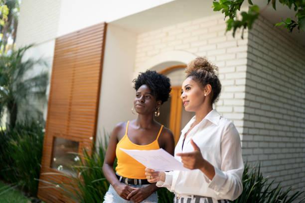 makelaar/financieel adviseur in gesprek met een klant voor een huis - verkoopster stockfoto's en -beelden