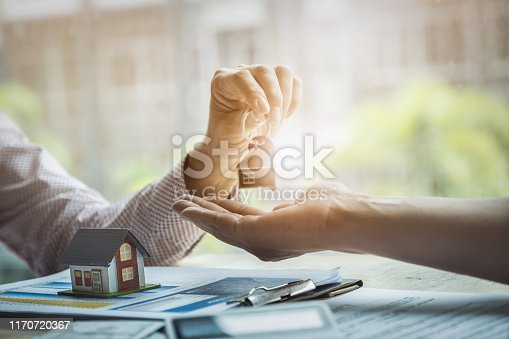 istock Real estate agents agree to buy a home and give keys to clients at their agency's offices. agreement and contract concept. 1170720367