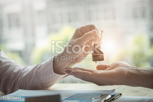 istock Real estate agents agree to buy a home and give keys to clients at their agency's offices. agreement and contract concept. 1170720472