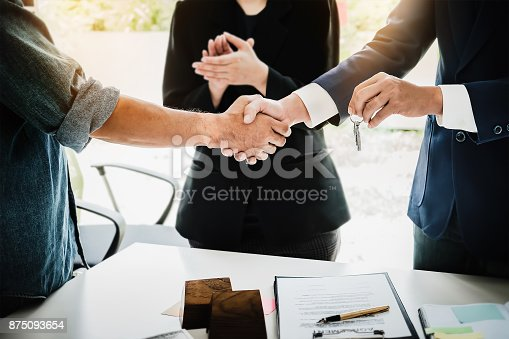 istock Real estate agents agree to buy a home and give keys to clients at their agency's offices. Concept agreement 875093654