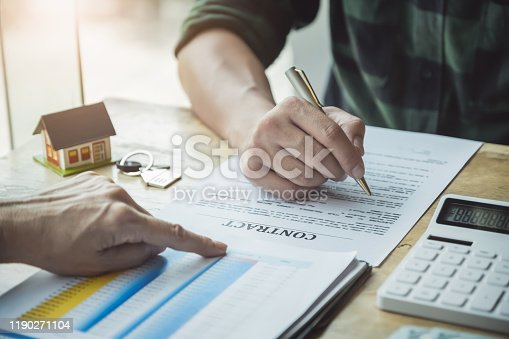 istock Real estate agents discussing about loans and interest rates for buying houses for customers who come to contact. contract and agreement concepts. 1190271104