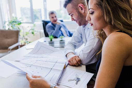 938640610 istock photo Real estate agents examining blueprints 1180087263