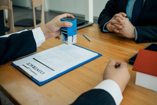 Immobilienmakler mit automatischem Stempel für die Einreichung von Dokumenten für die Kunden für einen Kaufvertrag zu unterzeichnen, Immobilienkonzept.