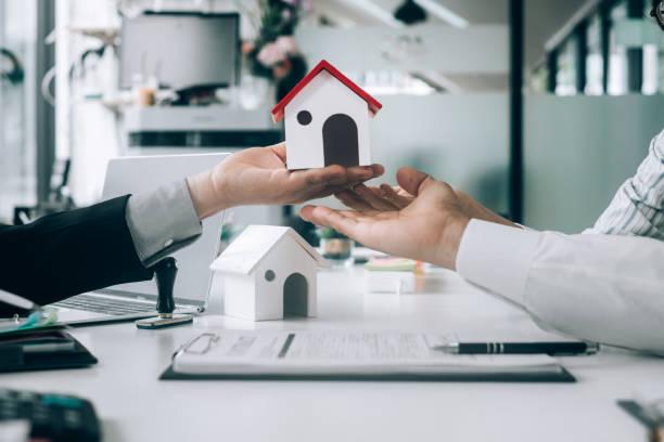 Immobilienmakler halten Modellhaus und geben für Kunden mit Kaufvertrag, Immobilienkonzept.