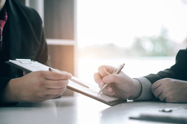 Immobilienmakler reichen Unterlagen ein, die Kunden für einen Kaufvertrag, ein Immobilienkonzept, unterzeichnen können.