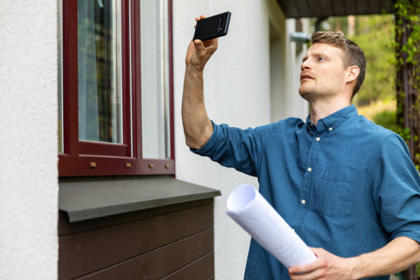 real estate appraiser taking pictures of property with phone stock photo