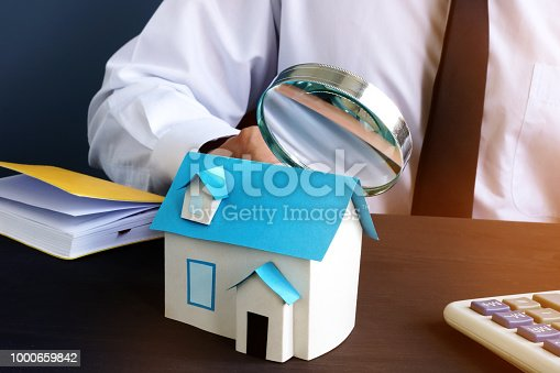 istock Real estate assessment. Man looking  at model of house. 1000659842
