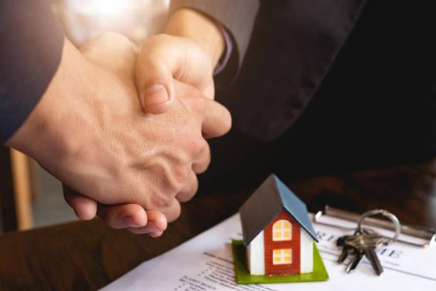Immobilienmakler und Kunde schütteln die Hände nach Vertragsunterzeichnung-Immobilien, Eigenheimkredite und Versicherungskonzept – Foto