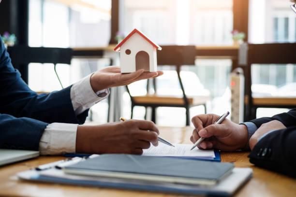 onroerende goederenmakelaar verklaar contract investering alvorens een contract huisvestingslandgoed in bureau te ondertekenen. contract en overeenkomst concept. - notaris stockfoto's en -beelden