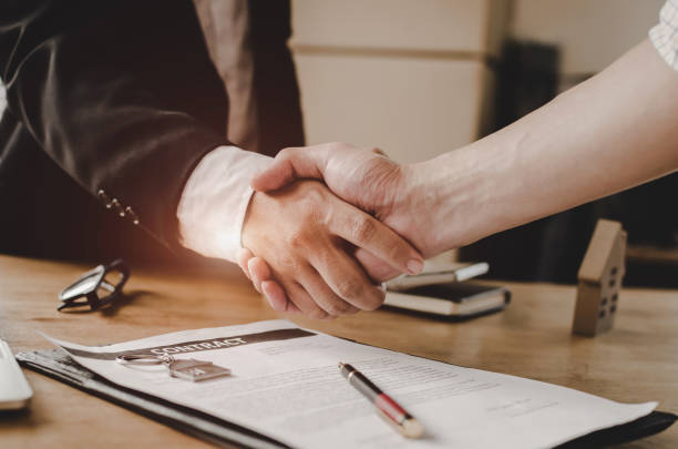 real estate broker manager hand shake with young man customer after signing contract for buying house in estate agent office, business, investment, home loan contract, buy and sell house concept - real estate law stock photos and pictures