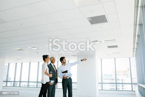 istock Real estate broker showing office space to clients 685774732