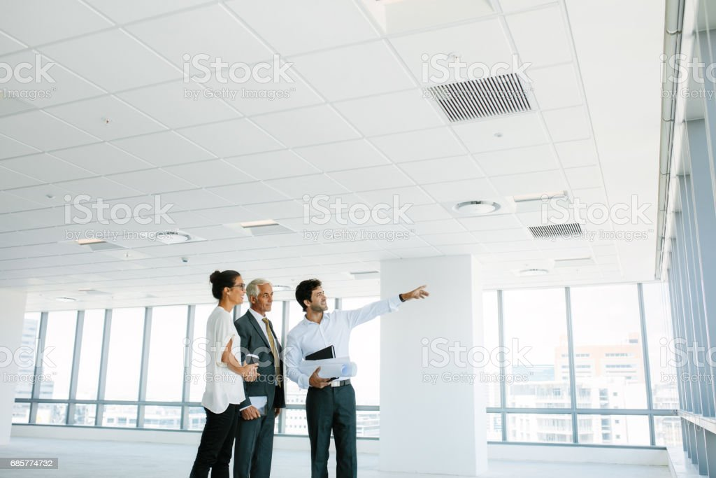Real estate broker showing office space to clients - foto de stock