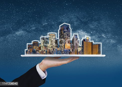 684793898 istock photo Real estate business, building technology and smart city. Businessman hand holding digital tablet with buildings hologram 1141208340