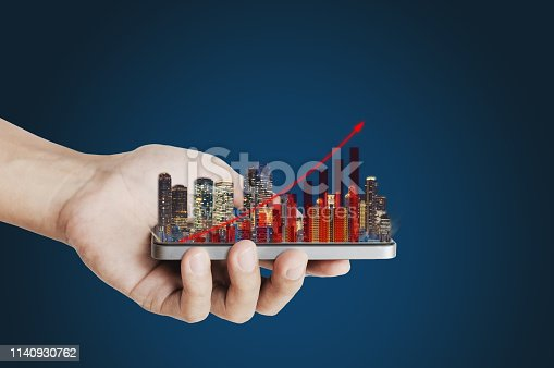 Real estate business investment concept. Hand holding mobile smart phone with buildings hologram and increasing bar chart and graph