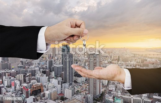 istock Real estate business, residential rental and investment. Businessman handover keys, with city sunrise background 1139659283