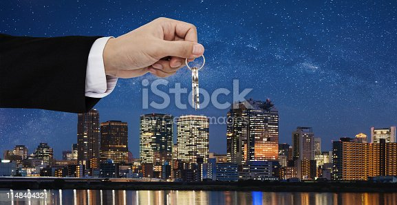 684793898 istock photo Real estate business, residential rental and investment. Businessman handover keys, with city at night background 1148404321
