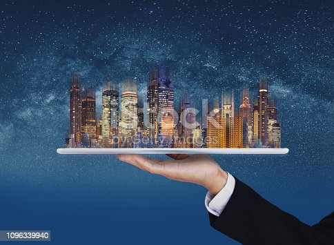 Real estate business, smart city, and building technology. Businessman hand holding digital tablet with buildings hologram and stars background