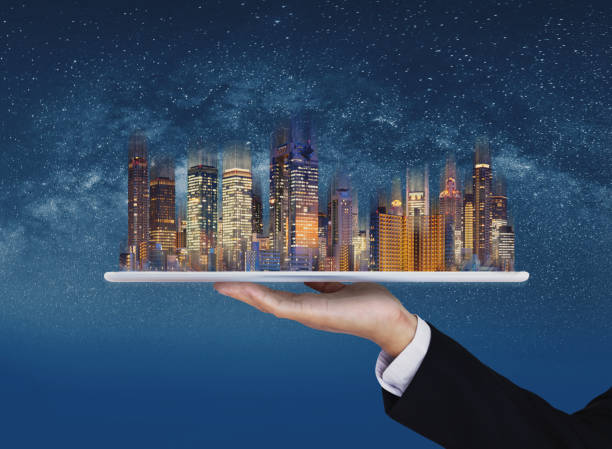 Real estate business, smart city, and building technology. Businessman hand holding digital tablet with buildings hologram and stars background stock photo