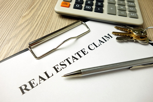 istock Real estate claim form with pen keys and calculator 1204616846