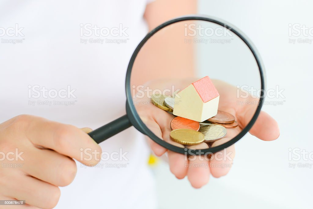 Real estate concept - coins and house under magnifying glass stock photo