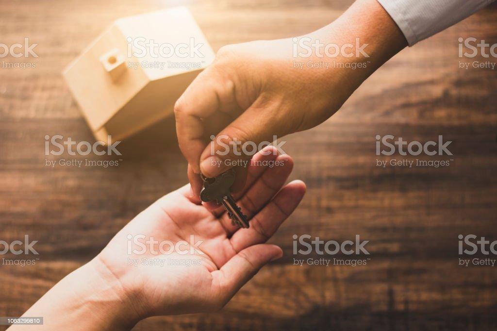 concept immobilier, banquier maison Agence offrent une clé de la maison propriétaire ou acheteur sur table en bois dans ton vintage photo libre de droits