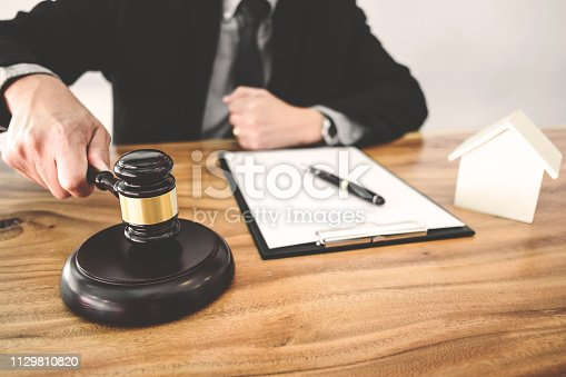 istock Real Estate concept, judge gavel / lawyer in auction with house model 1129810820
