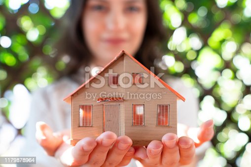 real estate concept with businesswoman holding mini house