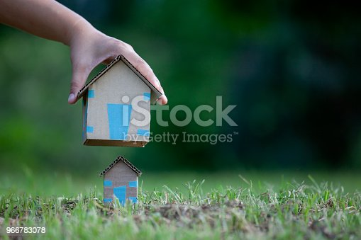istock Real estate concept woman holding big house for replace small house 966783078
