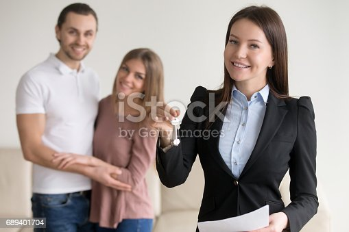 689401592 istock photo Real estate deal. Female smiling realtor showing keys to flat 689401704