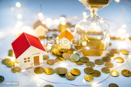 istock Real estate investment concept. Property marketing during festive holiday season. Hourglass with gold coins, house models and decorative lights on the table. Saving money for retirement. 1128824853