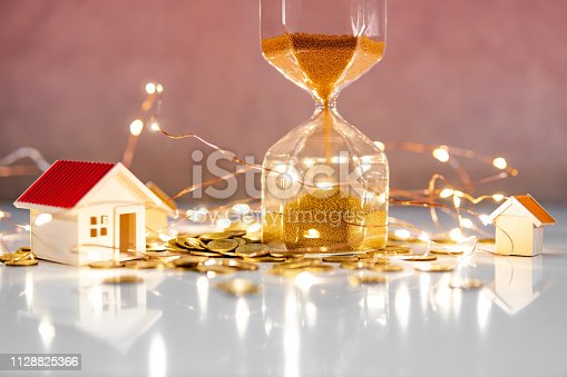 istock Real estate investment concept. Property marketing during festive holiday season. Hourglass with gold coins, house models and decorative lights on the table. Saving money for retirement. 1128825366