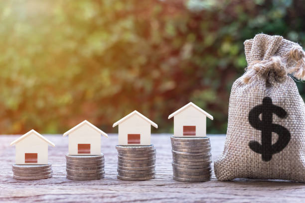 Real estate investment, home loan, mortgage, housing concept. Real estate investment, home loan, mortgage, housing concept. House model on stack of coins and US dollar money bag, Depicts saving and money management for house buying or home repay debt in future. depreciation stock pictures, royalty-free photos & images
