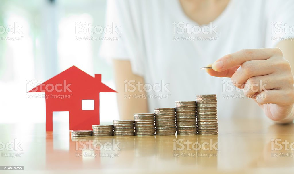 Real estate investment. House and coins on table. stock photo