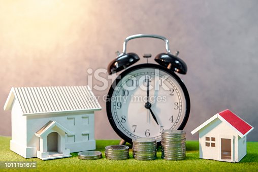 istock Real estate investment or Home mortgage loan rate. Property ladder concept. Coins stack, house model and table clock on green grass. Investment and business growth background 1011151672