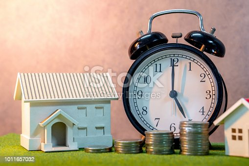 istock Real estate investment or Home mortgage loan rate. Property ladder concept. Coins stack, house model and table clock on green grass. Investment and business growth background 1011657032