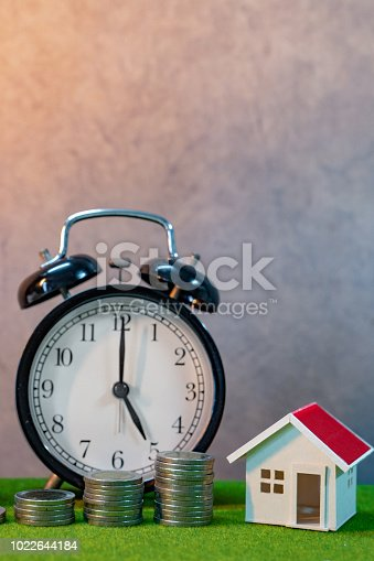 istock Real estate investment or Home mortgage loan rate. Property ladder concept. Coins stack, house model and table clock on green grass. Investment and business growth background 1022644184