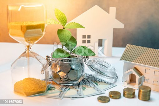istock Real estate investment or property ladder. Home mortgage loan rate. Saving money for future concept. Plant growing out of coins in glass jar with dollar banknotes, hourglass and house model on table 1011657060