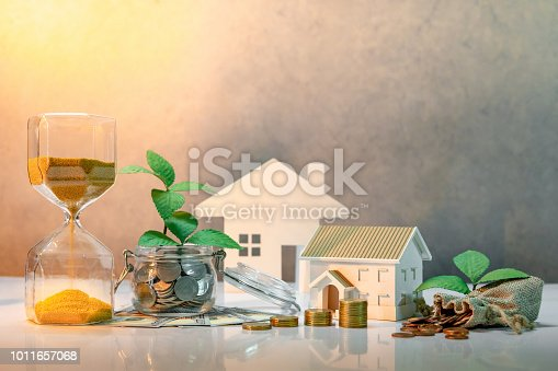 istock Real estate investment or property ladder. Home mortgage loan rate. Saving money concept. Plant growing out of coins in glass jar with dollar banknotes, hourglass, money bag and house model on table 1011657068
