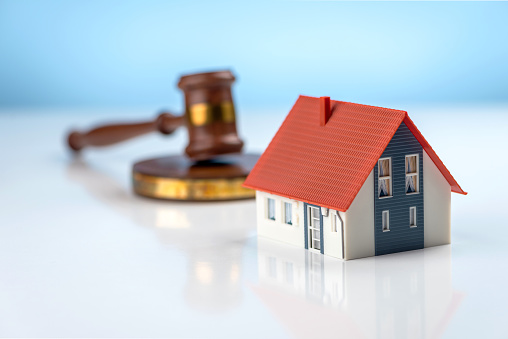 A judge hammer and a house on a blue background. Real estate law and house auction concepts
