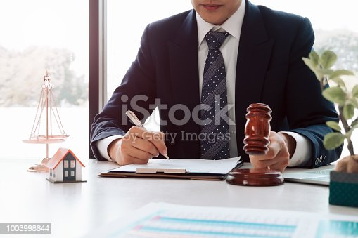 istock Real Estate Law concept. Gavel on sounding block in hand's Male judge at a courtroom, working for the insurance compensations. report the case on table in modern office. 1003998644