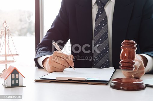 1050485096 istock photo Real Estate Law concept. Gavel on sounding block in hand's Male judge at a courtroom, working for the insurance compensations. report the case on table in modern office. 1003998646