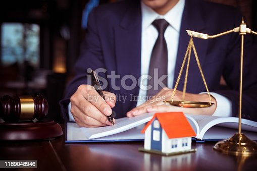Real Estate Law concept. Gavel on sounding block in hand's Male judge at a courtroom, working for the insurance compensations. report the case on table in modern office.