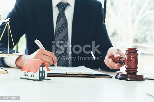istock Real Estate Law concept. Gavel on sounding block in hand's Male judge at a courtroom, working for the insurance compensations. report the case on table in modern office. 995778920
